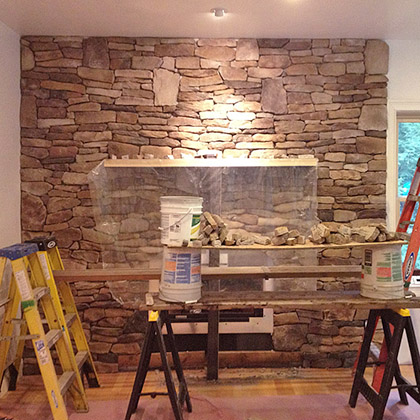 custom fireplace installation with faux stone wall surround and gas fireplace insert